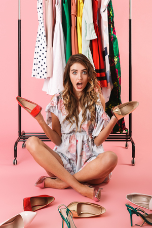 Full length photo of puzzled woman in dress sitting under wardrobe rack with shoes isolated over pink background Фото со стока - 119988215