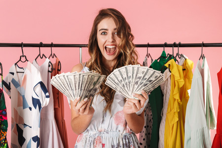 Image of happy girl standing near wardrobe while holding money fans isolated over pink background