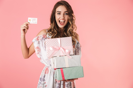Image of joyful woman 20s in dress holding credit card and boxes with purchase, isolated over pink background Stock Photo