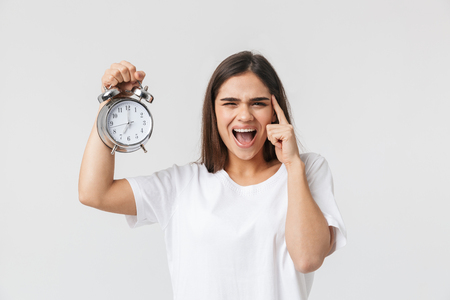 Angry young girl standing isolated over white background, showing alarm clock Foto de archivo - 119988665