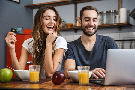 Cheerfuly young couple shopping with laptop and credit card while having breakfast