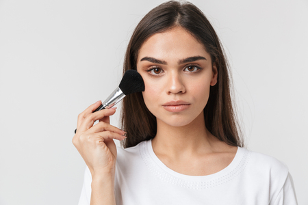 Close up portrait of a pretty young woman casualy dressed isolated over white, applying makeup with a brush Stock Photo