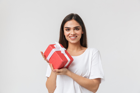 Portrait of a beautiful young woman casualy dressed standing isolated over white background, holding gift box