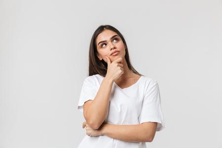 Portret van een mooie peinzende jonge vrouw terloops gekleed staand geïsoleerd op een witte achtergrond