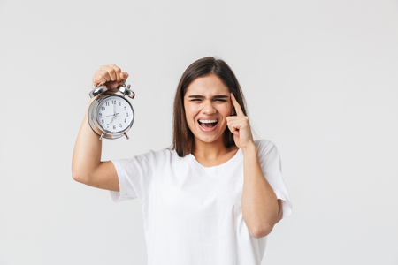 Angry young girl standing isolated over white background, showing alarm clock