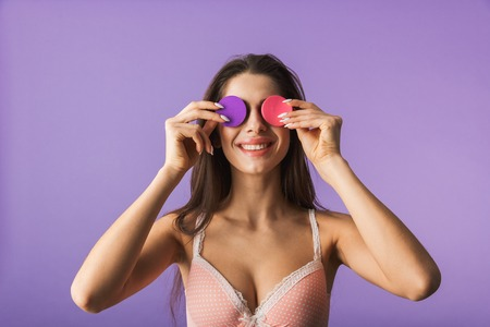 Beautiful sensual brunette woman wearing lingerie standing isolated over violet background, holding makeup sponges Stock Photo