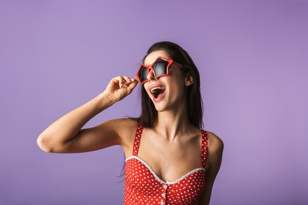 Beautiful brunette woman wearing lingerie and star shaped sunglasses standing isolated over violet background, posing Фото со стока