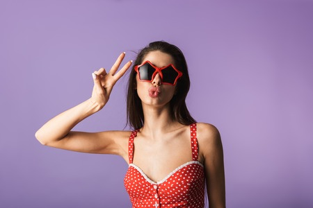 Beautiful brunette woman wearing lingerie and star shaped sunglasses standing isolated over violet background, posing Stock Photo