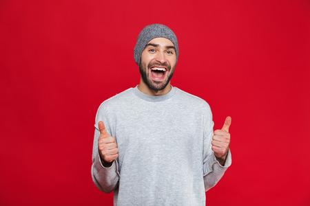 Bild eines attraktiven Mannes der 30er Jahre, der Stoppeln hat, lachen und Daumen nach oben auf der Kamera zeigen, isoliert auf rotem Hintergrund