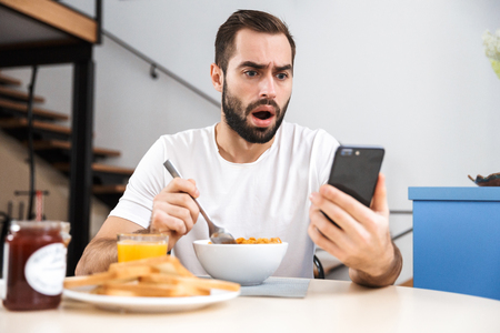 Handsome shocked young man having breakfast while sitting at the kitchen, holding mobile phone Stockfoto - 119991287