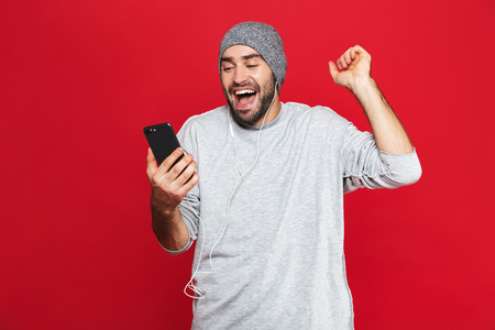 Image of unshaved man 30s in casual wear holding cell phone and listening to music with headphones isolated over red background Imagens