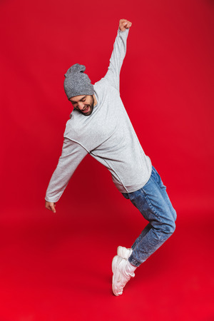 Full length photo of joyful man 30s in casual wear smiling and jumping isolated over red background
