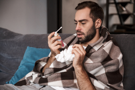 Photo of upset man 30s wrapped in blanket having temperature and being ill while sitting on sofa in apartment
