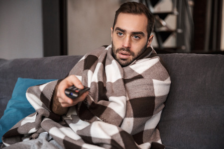 Photo of bearded man 30s having temperature and being ill while sitting wrapped in blanket on sofa at home