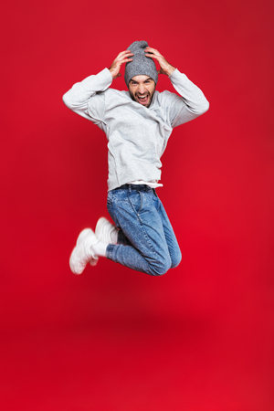 Full length photo of handsome man 30s in casual wear smiling and jumping isolated over red background Stock Photo