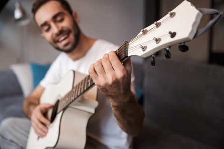 Photo of handsome man 30s wearing casual t-shirt playing acoustic guitar while sitting on sofa in apartment Reklamní fotografie