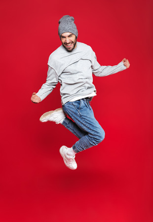 Full length photo of optimistic man 30s in casual wear smiling and jumping isolated over red background