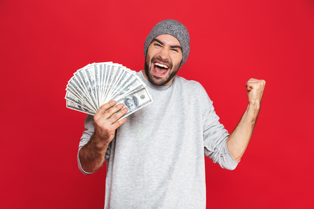 Photo of lucky guy 30s in casual wear rejoicing and holding cash money isolated over red background Imagens