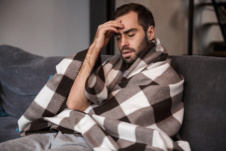 Photo of unhappy man 30s wrapped in blanket having temperature and looking sick while sitting on sofa in apartment