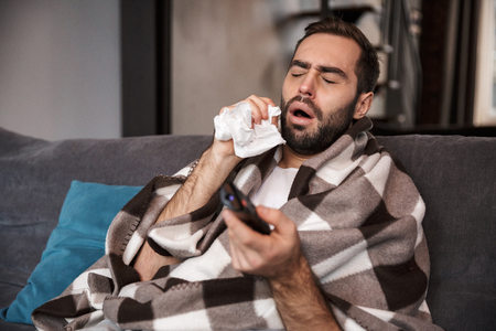 Photo of sick man 30s wrapped in blanket having temperature and being ill while sitting on sofa in apartment Banco de Imagens