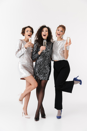 Image of a beautiful young happy women friends posing isolated over white wall background drinking champagne on a party. Stock Photo
