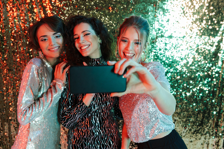 Three cheerful beautiful women wearing bright clothes having a party over sparkling background, taking a selfie