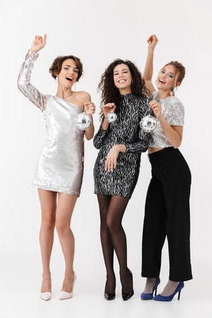 Image of a beautiful young happy women friends posing isolated over white wall background holding little disco balls on a party.