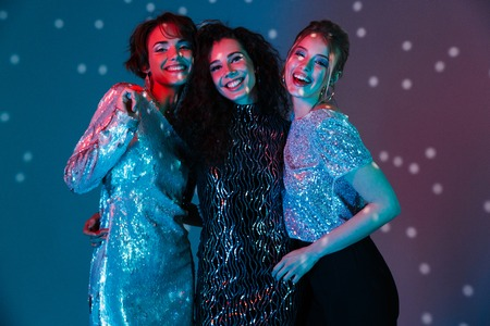 Image of a beautiful young happy women posing isolated with disco ball lights. Banco de Imagens