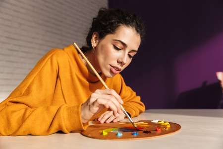 Smiling artistic woman choosing paint color on a palette indoors Imagens