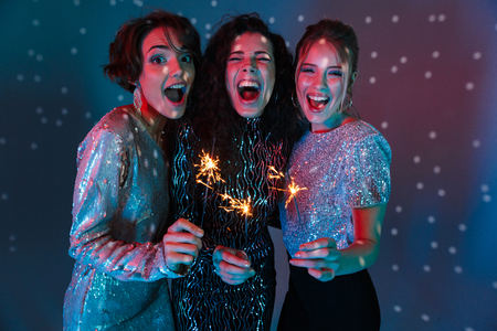 Three cheerful beautiful women wearing bright clothes having a party over sparkling background, holding sparklers Stock Photo