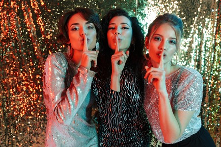 Three cheerful beautiful women wearing bright clothes having a party over sparkling background Stock Photo