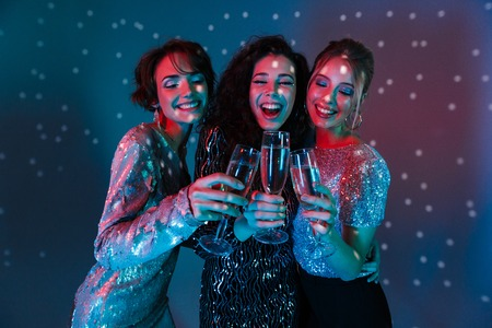 Image of a beautiful young happy women posing isolated with disco ball lights holding glasses with champagne. Stock Photo