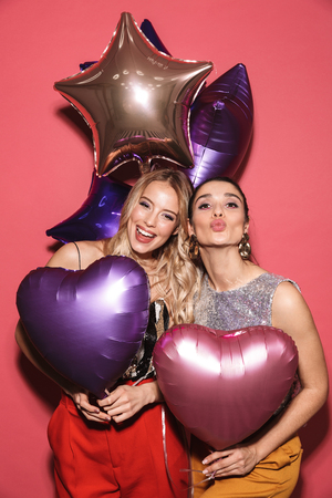 Image of two young girls 20s in stylish outfit laughing and holding festive balloons isolated over red background