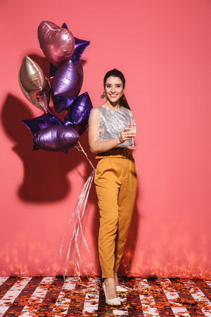 Portrait of elegant woman 20s in stylish outfit holding festive balloons and drinking champagne on party isolated over red background Imagens