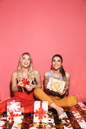 Portrait of two fancy women 20s in stylish outfit celebrating and sitting on floor with bunch of present boxes isolated over red background