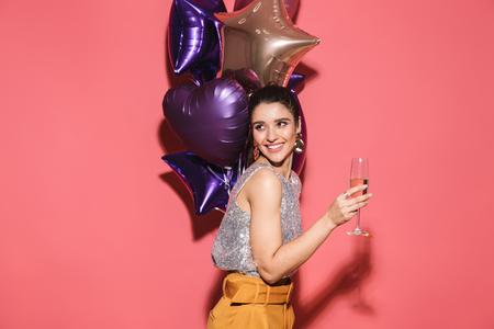 Portrait of attractive woman 20s in stylish outfit holding festive balloons and drinking champagne on party isolated over red background
