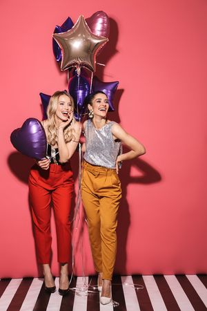 Image of two pretty girls 20s in stylish outfit laughing and holding festive balloons isolated over red background