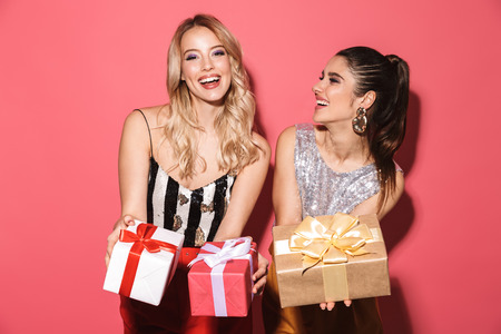 Portrait of two gorgeous girls 20s in stylish outfit on party holding gift boxes isolated over red background Imagens