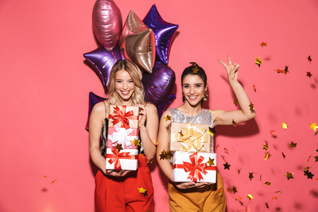 Portrait of two trendy women 20s in stylish outfit holding present boxes and balloons on party isolated over red background Stock Photo