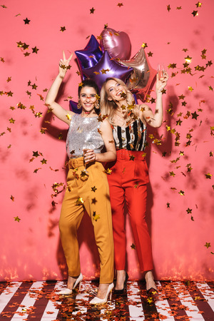 Photo of two glamour women 20s in stylish outfit holding festive balloons and drinking champagne on party isolated over red background