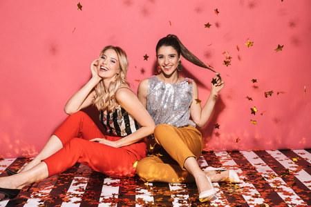 Portrait of two joyful women 20s in stylish outfit celebrating and sitting on floor with falling confetti isolated over red background Stock Photo