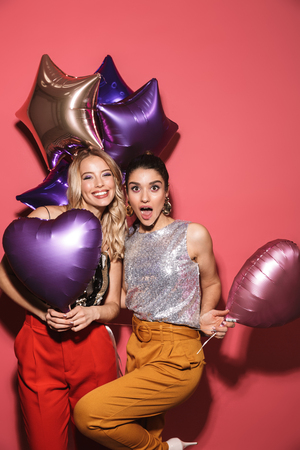 Image of two beautiful girls 20s in stylish outfit laughing and holding festive balloons isolated over red background Stock Photo