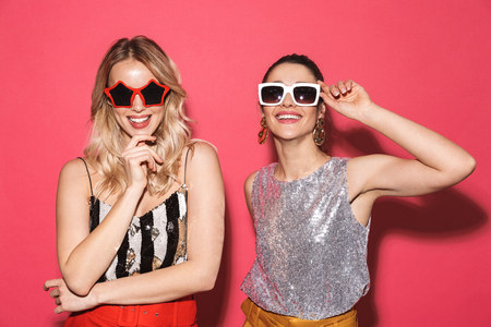 Photo of two posh women 20s in trendy outfit and sunglasses smiling at camera isolated over red background
