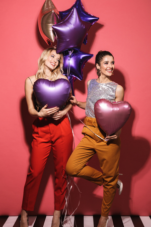 Image of two seductive girls 20s in stylish outfit laughing and holding festive balloons isolated over red background Stock Photo