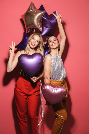 Image of two posh girls 20s in stylish outfit laughing and holding festive balloons isolated over red background Stock Photo