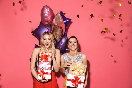 Portrait of two attractive women 20s in stylish outfit holding present boxes and balloons on party isolated over red background