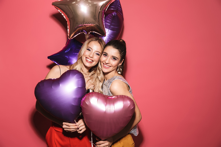 Image of two joyful girls 20s in stylish outfit laughing and holding festive balloons isolated over red background