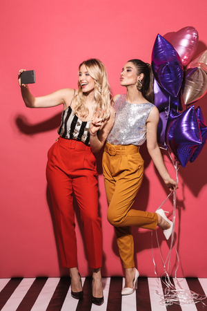 Image of two fashionable girls 20s in stylish outfit holding festive balloons and taking selfie photo isolated over red background