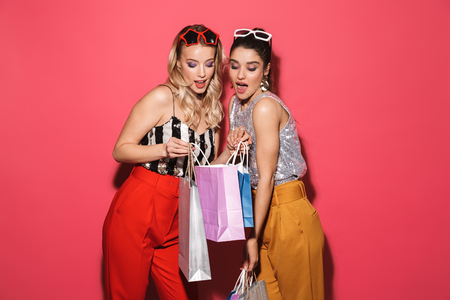 Photo of two european women 20s in trendy outfit holding colorful shopping bags isolated over red background