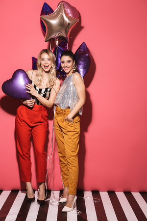 Image of two european girls 20s in stylish outfit laughing and holding festive balloons isolated over red background